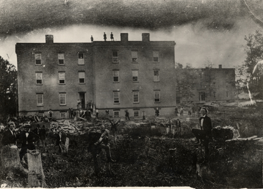 "This photograph shows students clearing the land around Saints' Rest. The text on the back of the photograph reads: ""Built 1857. Burned 1876."" Image courtesy of MSU Archives and Historical Collections."