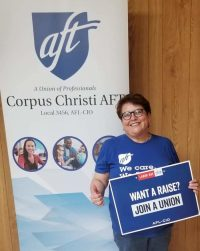 """Nancy Vera in front of CCAFT banner holding """"Want a Raise?"""" Sign"""