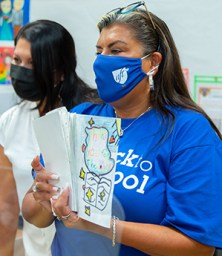 AFT Executive Vice President Evelyn DeJesus in blue union t-shirt reading to students