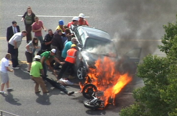 Biker rescued from under burning car: Video