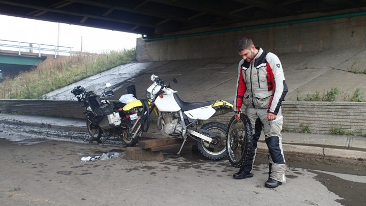 Shame, shame! Zac stands next to his incapacitated motorcycle after a front tire repair during D2D scouting. Photo: Rob Harris