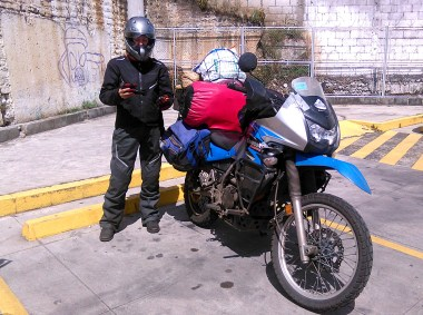 Tammy, roadside mid-trip with her KLR and her Icon gear.