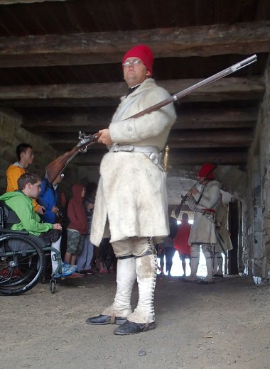 A guard keeps watch while the masses hear a talk on the workings of the musket.