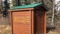 "[A photo of an outhouse, with the word ""MOSQUE"" spray-painted on the side.]"