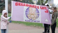 """[Photo of two women holdind up a flag - a white Canadian pale bordered by pink on both sides, with a happy cartoon foetus in the middle, across the top is written """"CELEBRATE LIFE WEEK"""", and across the bottom """"PLEASE LET ME LIVE"""", and there's a small white maple leaf in the bottom right.]"""