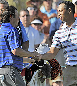 Tiger shakes the hand of Tim Clark while the world crumbles around him.