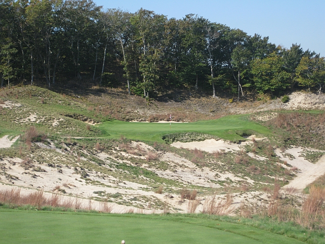 The dramatic, and slight, par-3 17th at Friar's Head shows off the natural dunes.