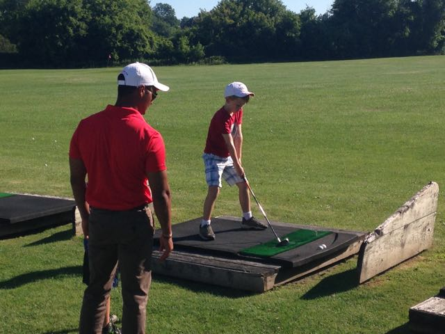 My son works on his swing while an instructor watches.
