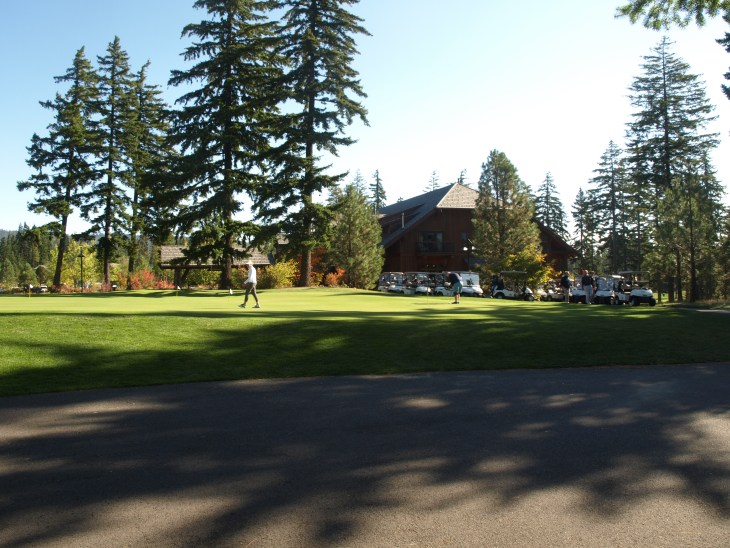 The clubhouse looms behind the practice green.