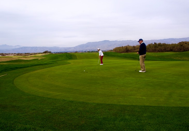 Steve looks on atop the expansive double green as Myra rolls her putt up hole high