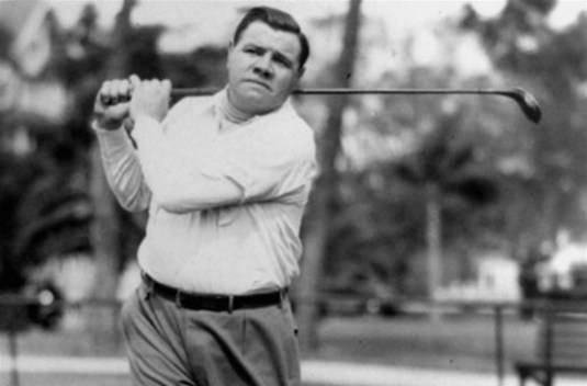 Babe Ruth swings a golf club.