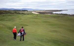 Royal Dornoch golf course golfer and caddy. (Image: One Ocean Expeditions)