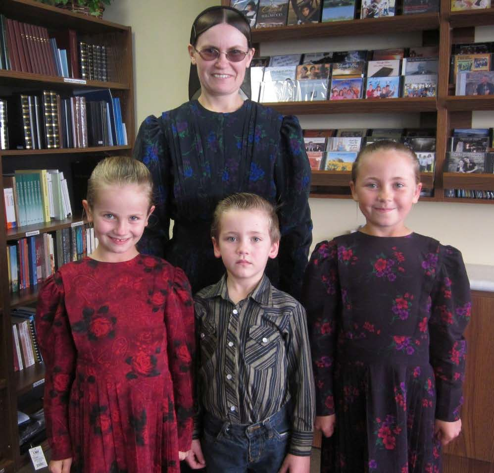 Photo of a woman and three children wearing traditional styles from their Mennonite community