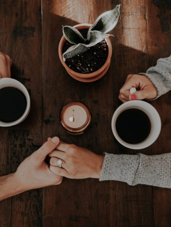 couple holding hands having coffee