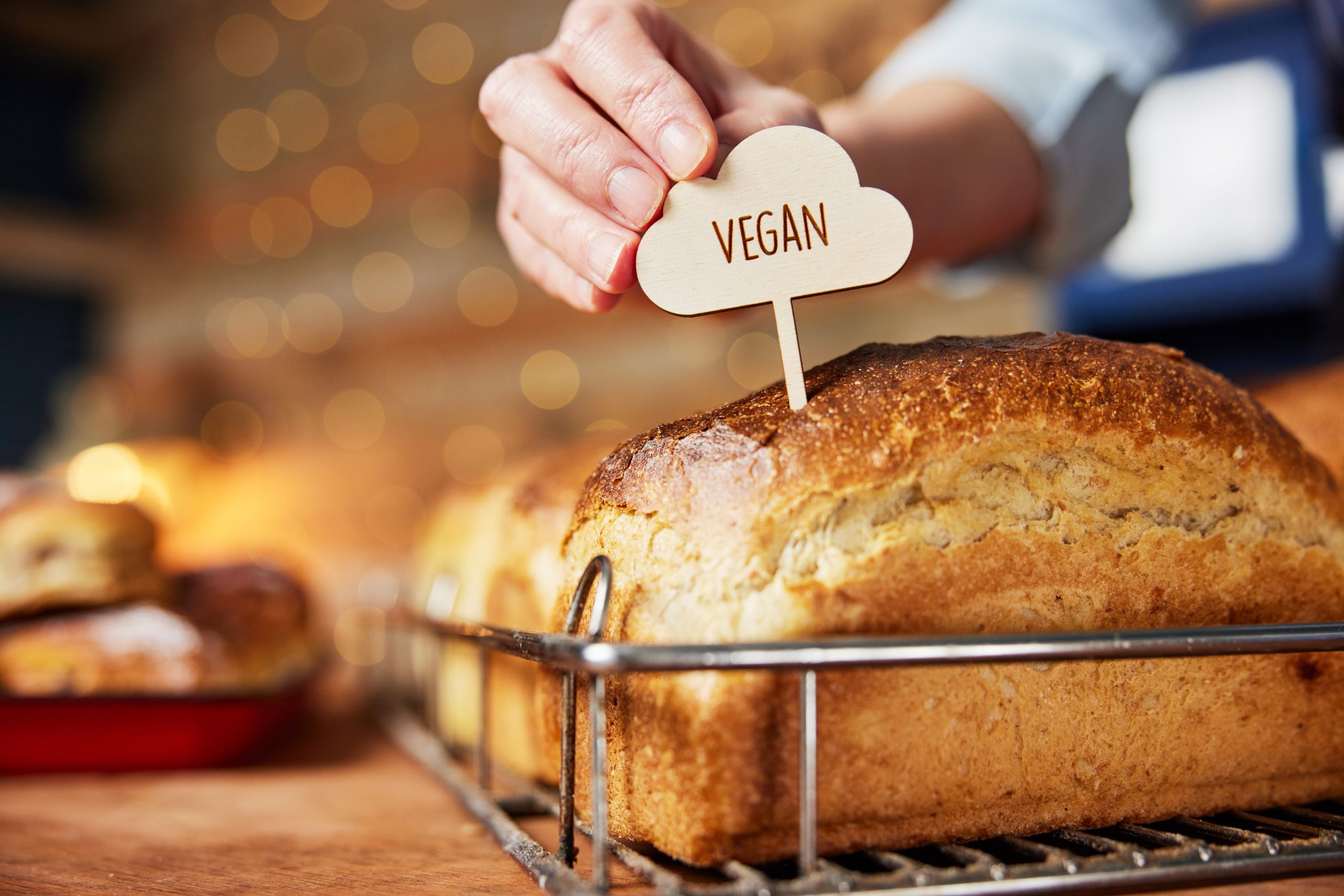 Sales Assistant In Bakery Putting Vegan Label Into Freshly Baked Baked