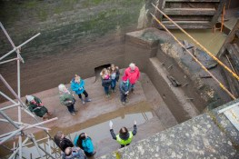 A group of visitors having things explained in the drained lock.