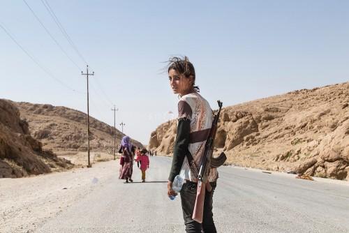 Chica Yezidi con un rifle protegiendo a su famiia contra EI