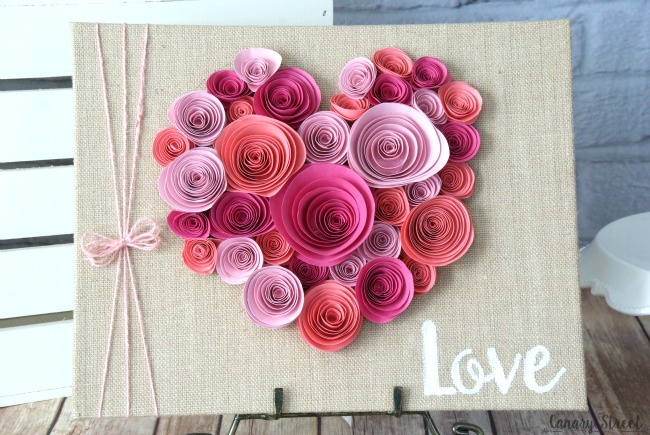 Curl paper flowers and glue them to a burlap canvas. Would be cute for Valentine's Day or even as wedding or bridal shower table decor. https://canarystreetcrafts.com/