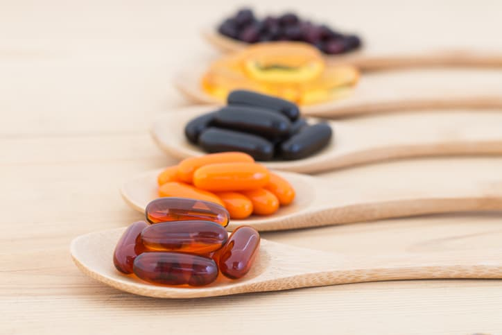 Healthy Vitamin supplement capsules in a spoons.