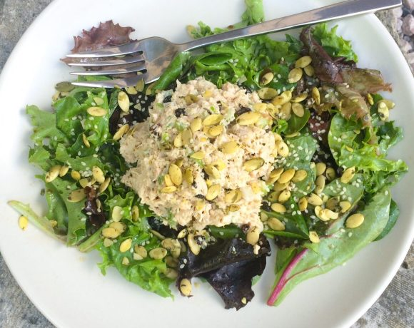 Tuna salad with seeds and currants over greens