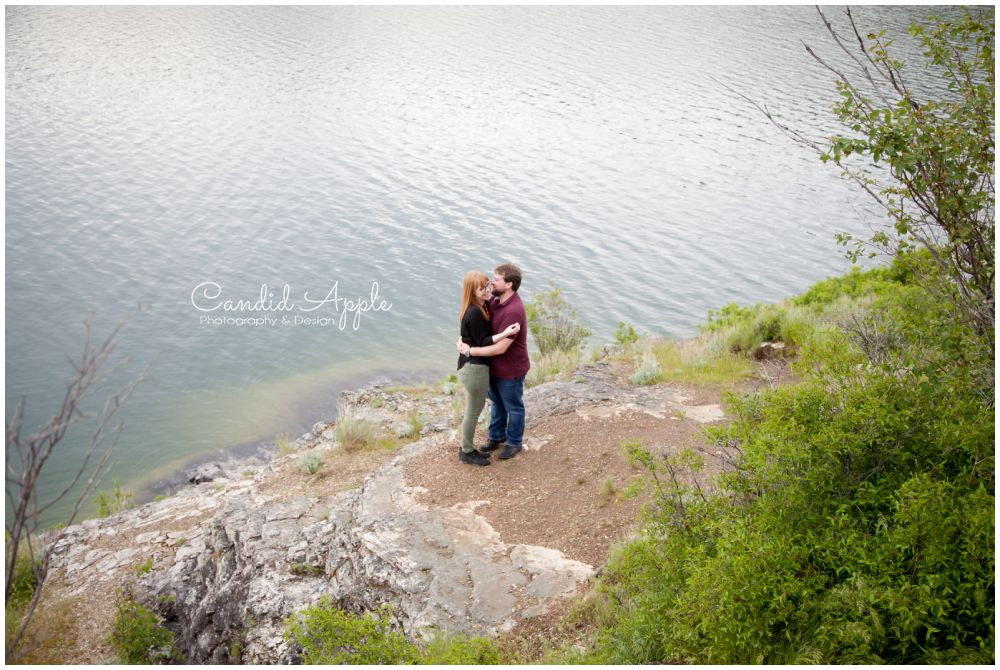 A sweet couple standing and kissing on the rocky lake's edge