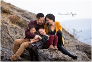 A Family Sitting On Rocks Snuggled and Giggling