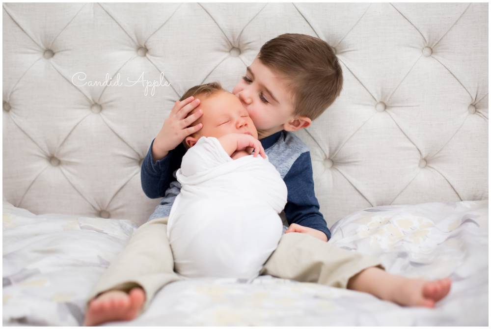 A little boy kissing his new baby brother