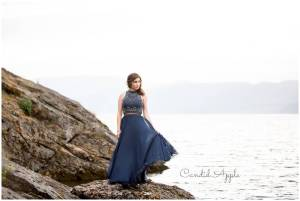 A Stunning woman graduating in a blue dress on the lakeshore rocks