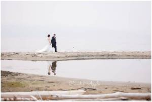 Bride and groom walking hand in hand along smokey shore
