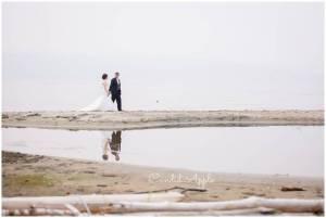 Bride and groom walking hand in hand along smokey shore