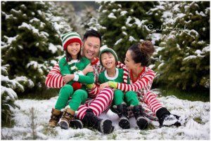 A family sitting in the snow at a tree farm wearing onesies
