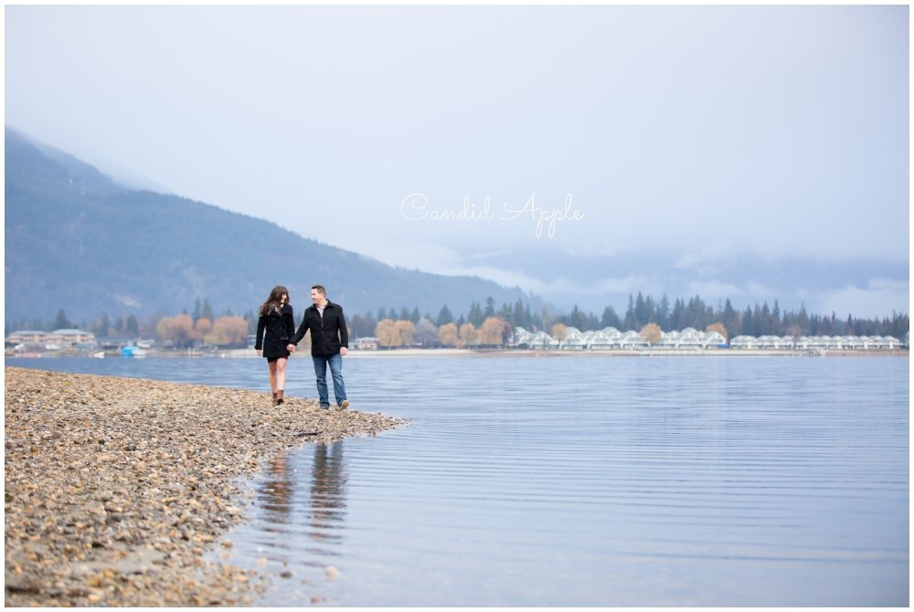 A couple walking along the shore of Mara Lake in Sicamous