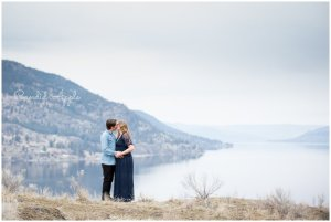 A couple standing on a mountain top kissing