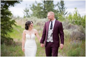 Bride and groom walking on a trail holding hands and looking at each other