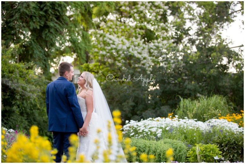 A couple standing together in a garden at sunset