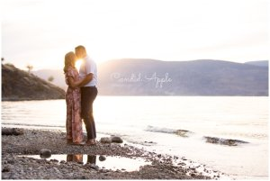 A couple standing on the lakeshore at sunset