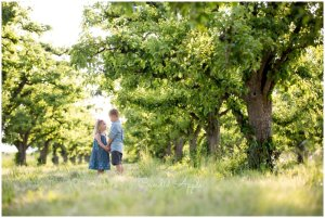 Siblings looking at each other in an orchard