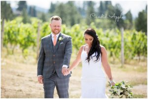 A couple holding hands while walking through a vineyard on their wedding day