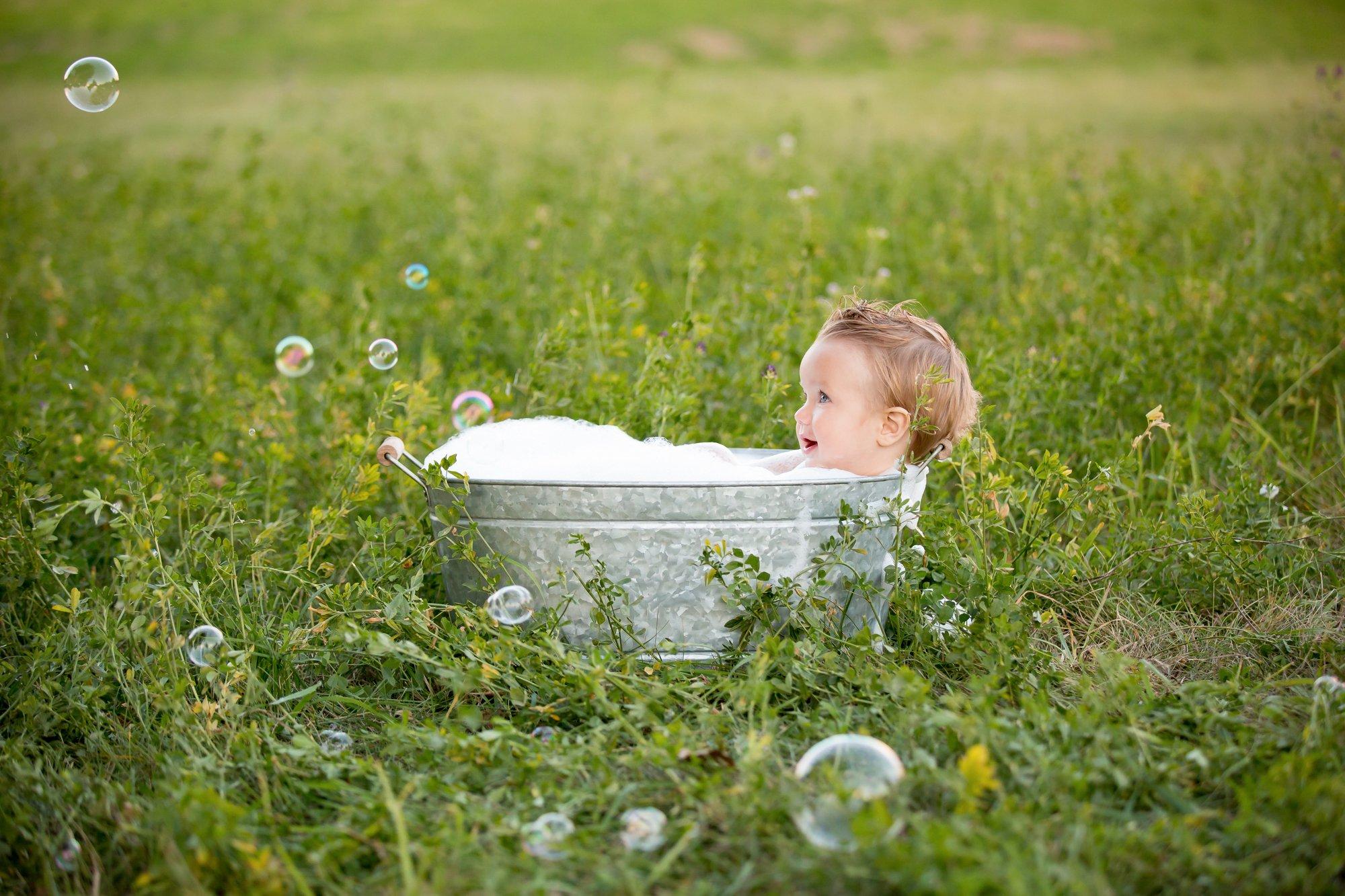 A little boy sitting in an outside bubble bath