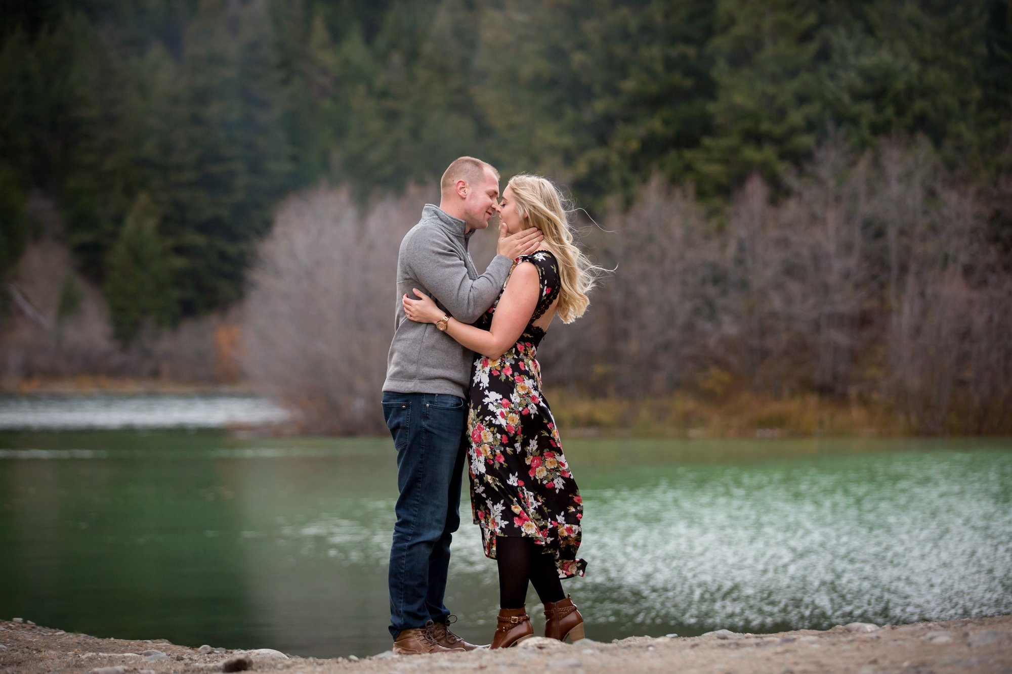 A couple about to kiss next to a green lake