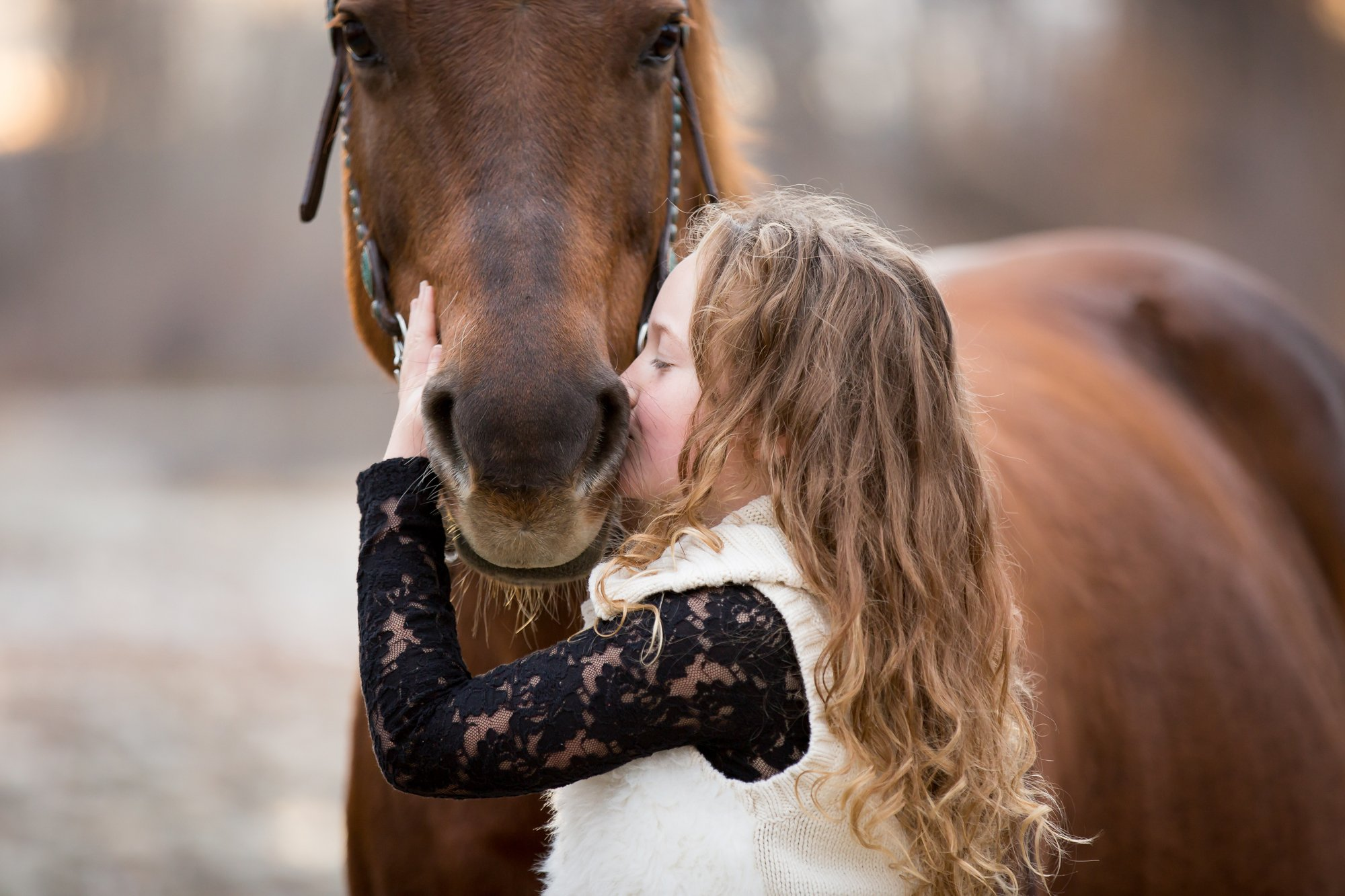 A girl kisssing her horse on the nose