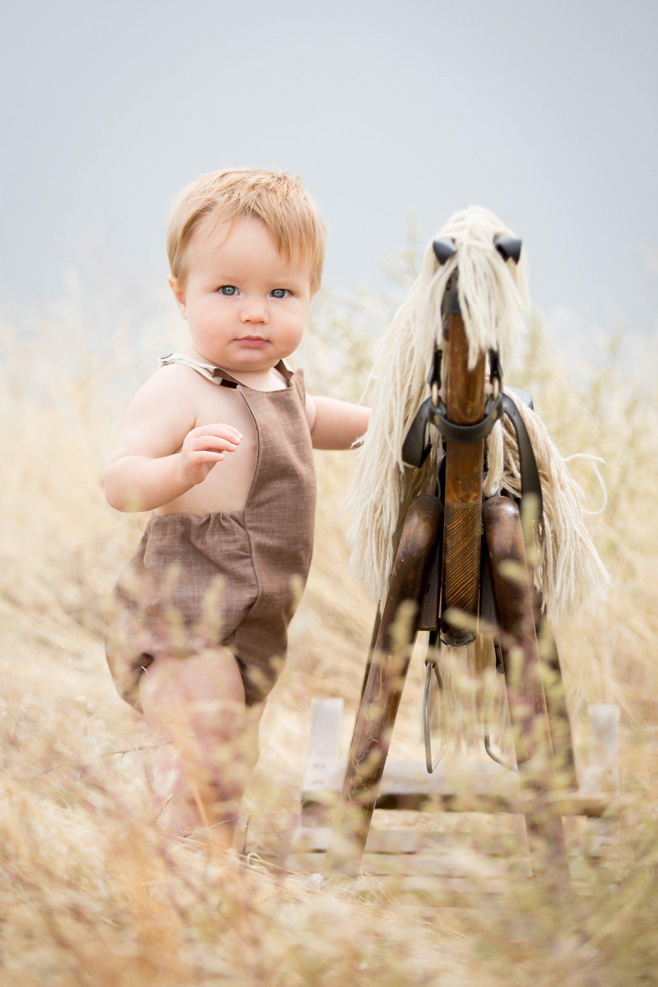 A little boy standing next to a rocking horse