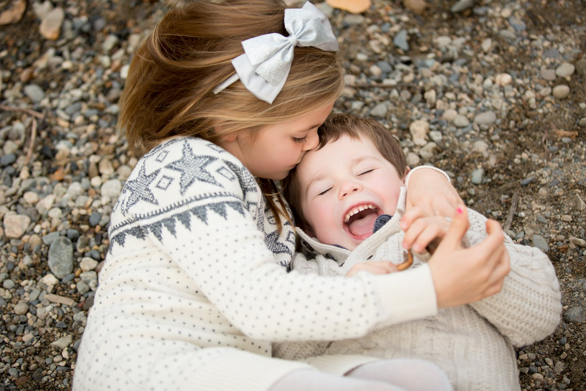 A brother and sister laying on the ground laughing