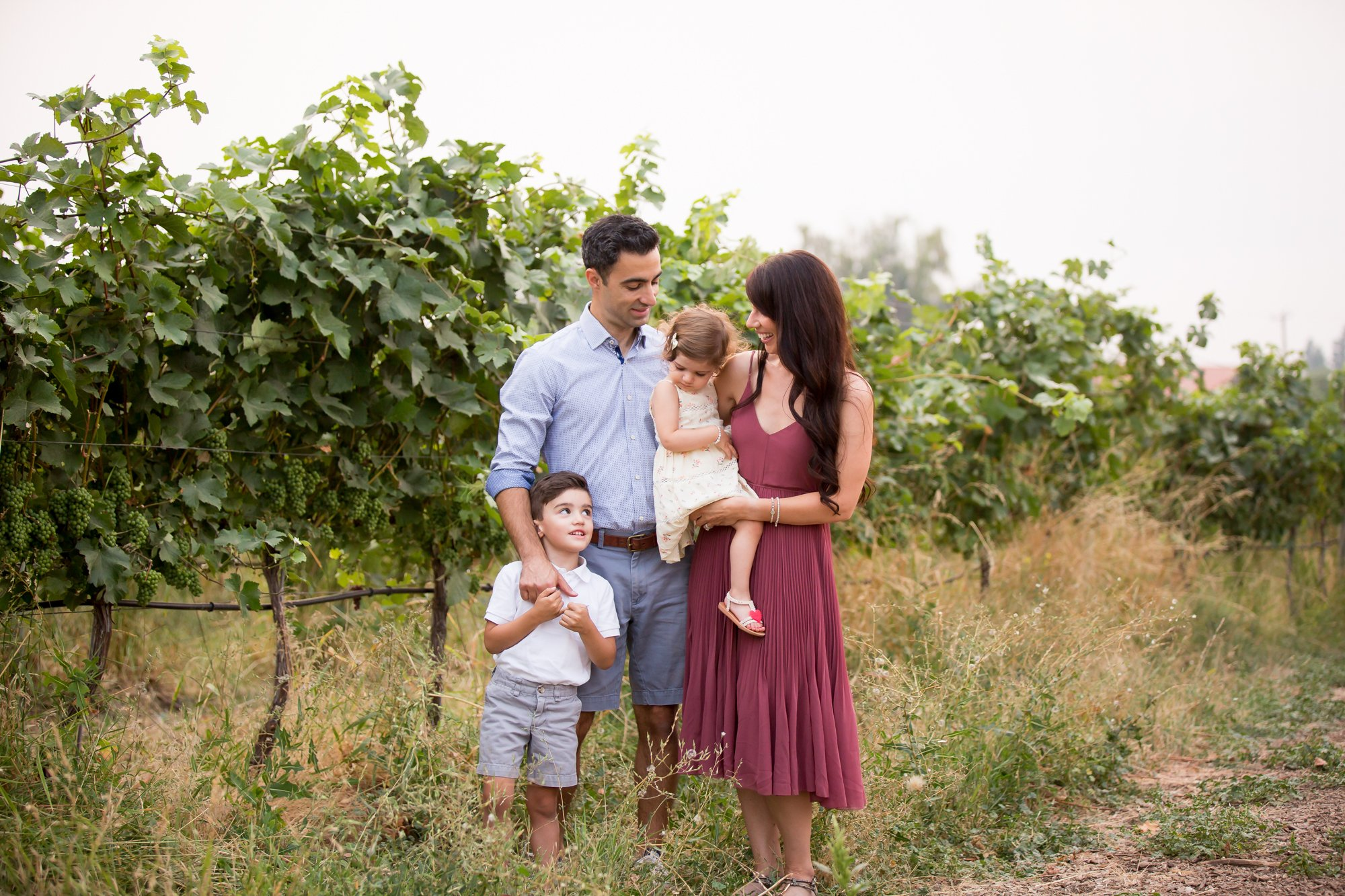 A family looking at each othe rin a vineyard
