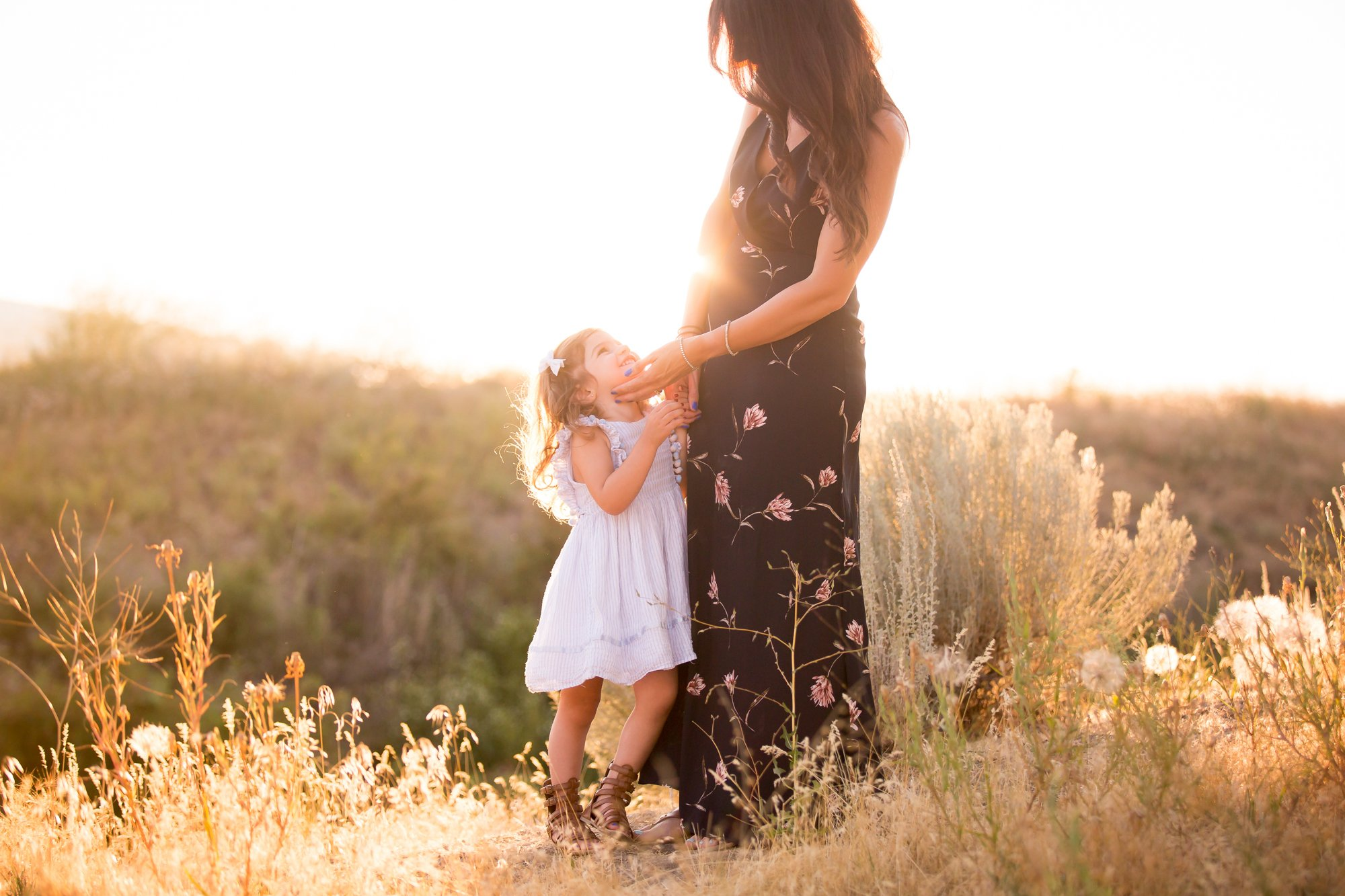 A mom and daughter standing on the sunlight
