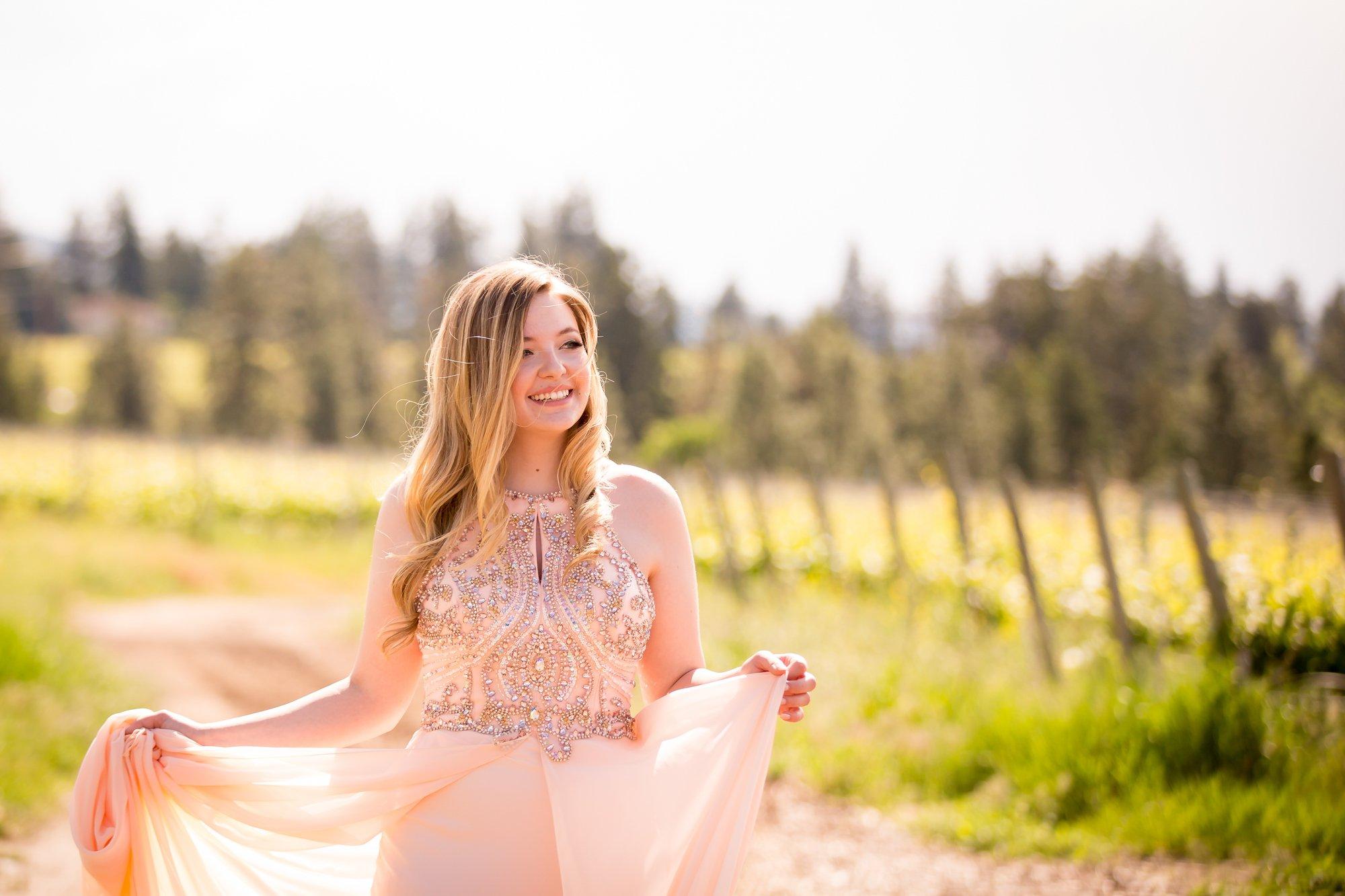 A grad walking int he sunlight in her pink dress