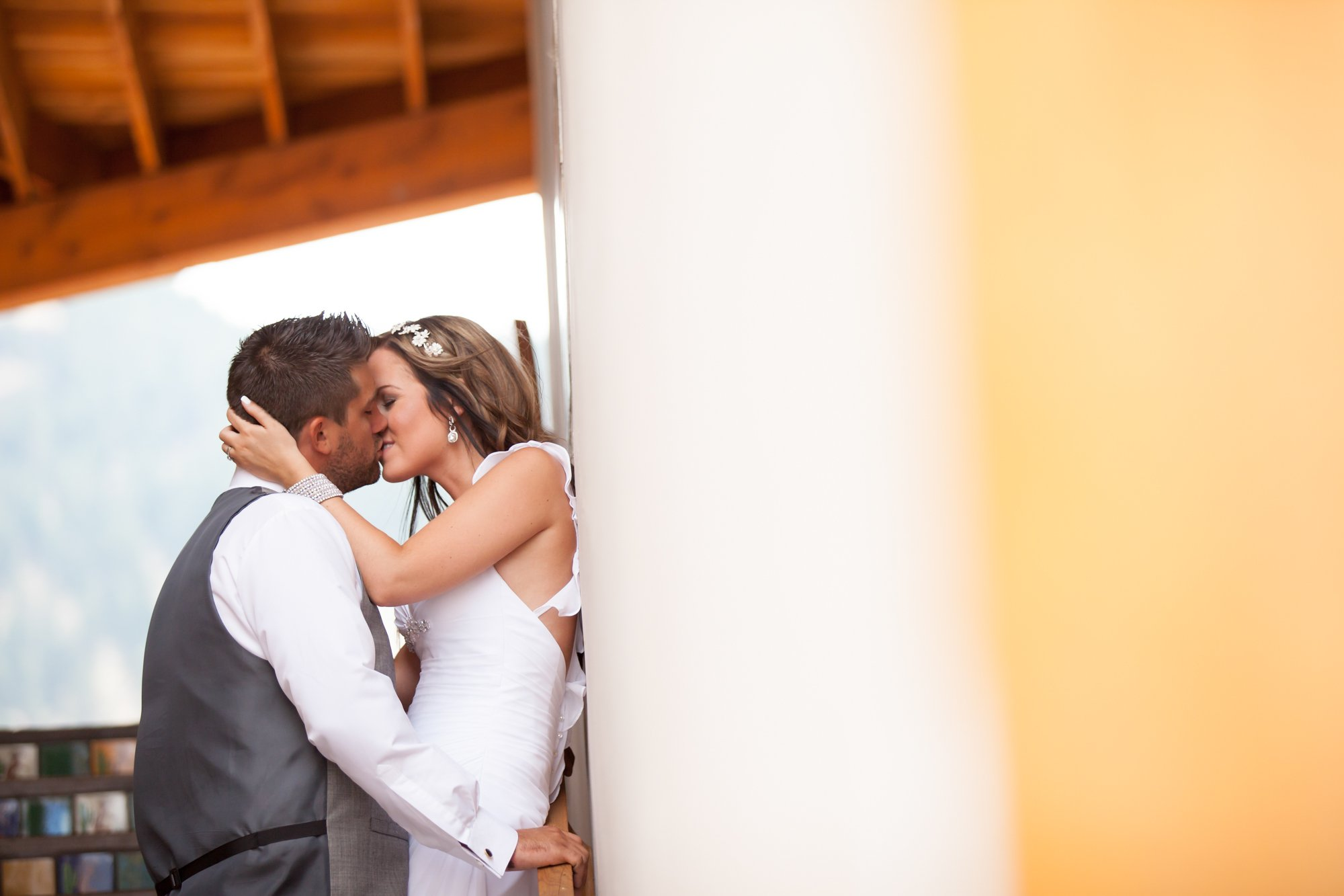 A bride kissing her groom against a wall
