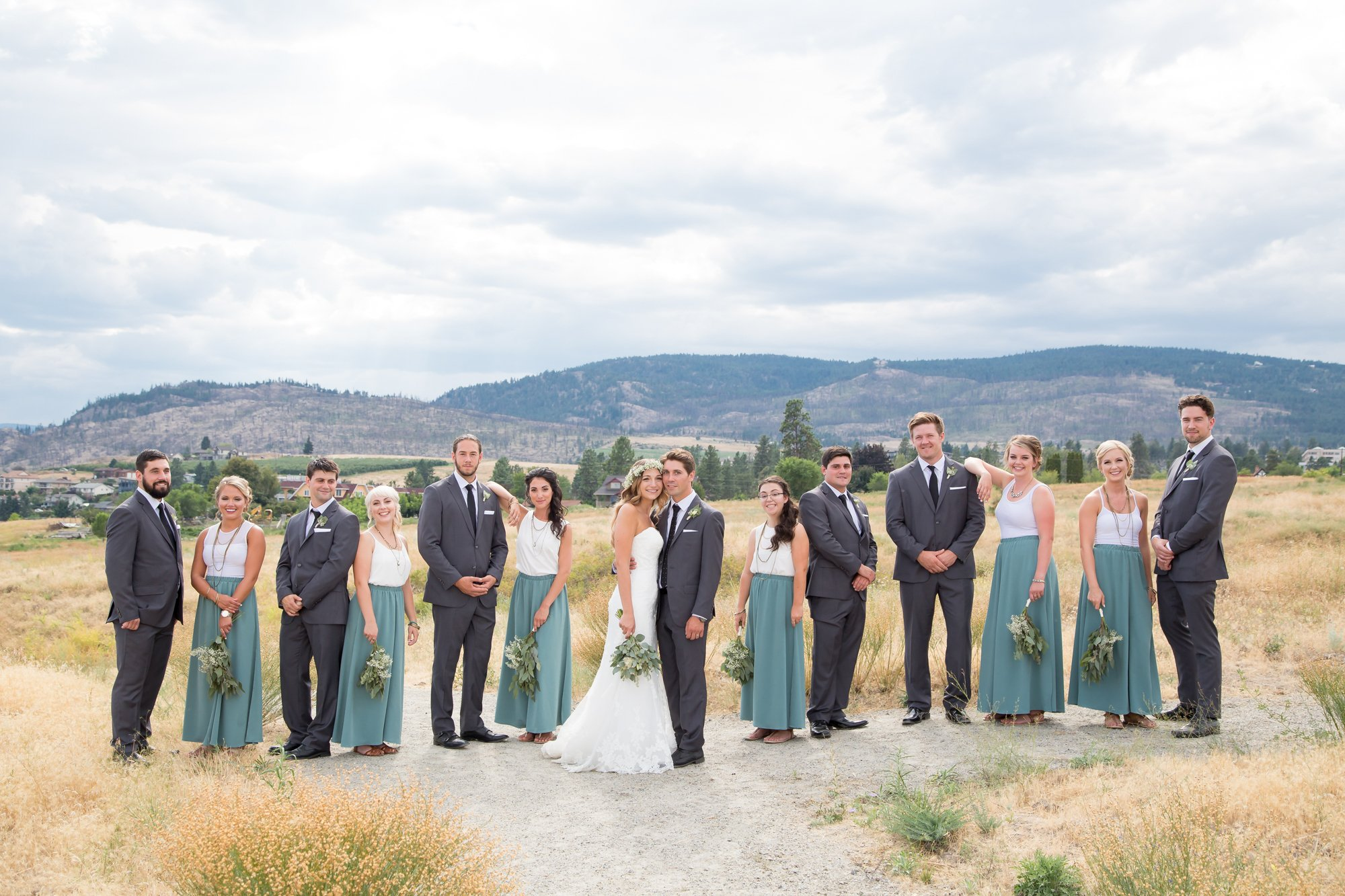 A large wedding party standing in an open field