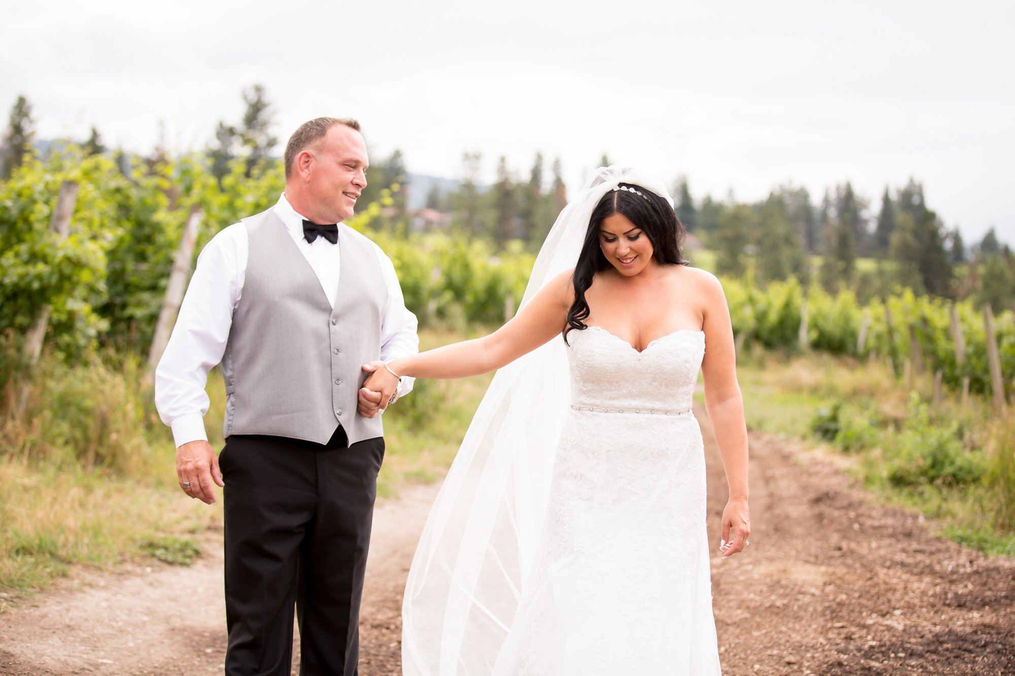 A bride and groom walking through a vineyard