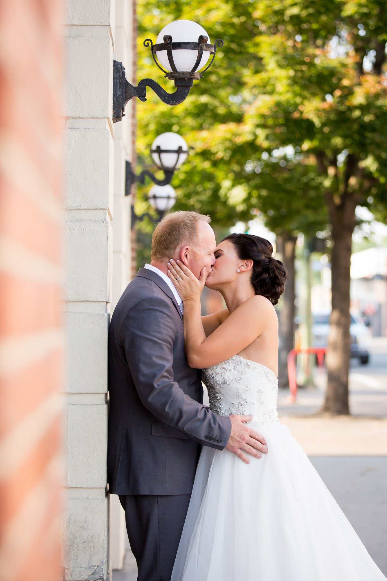 A bride and groom kissing against a brick wall
